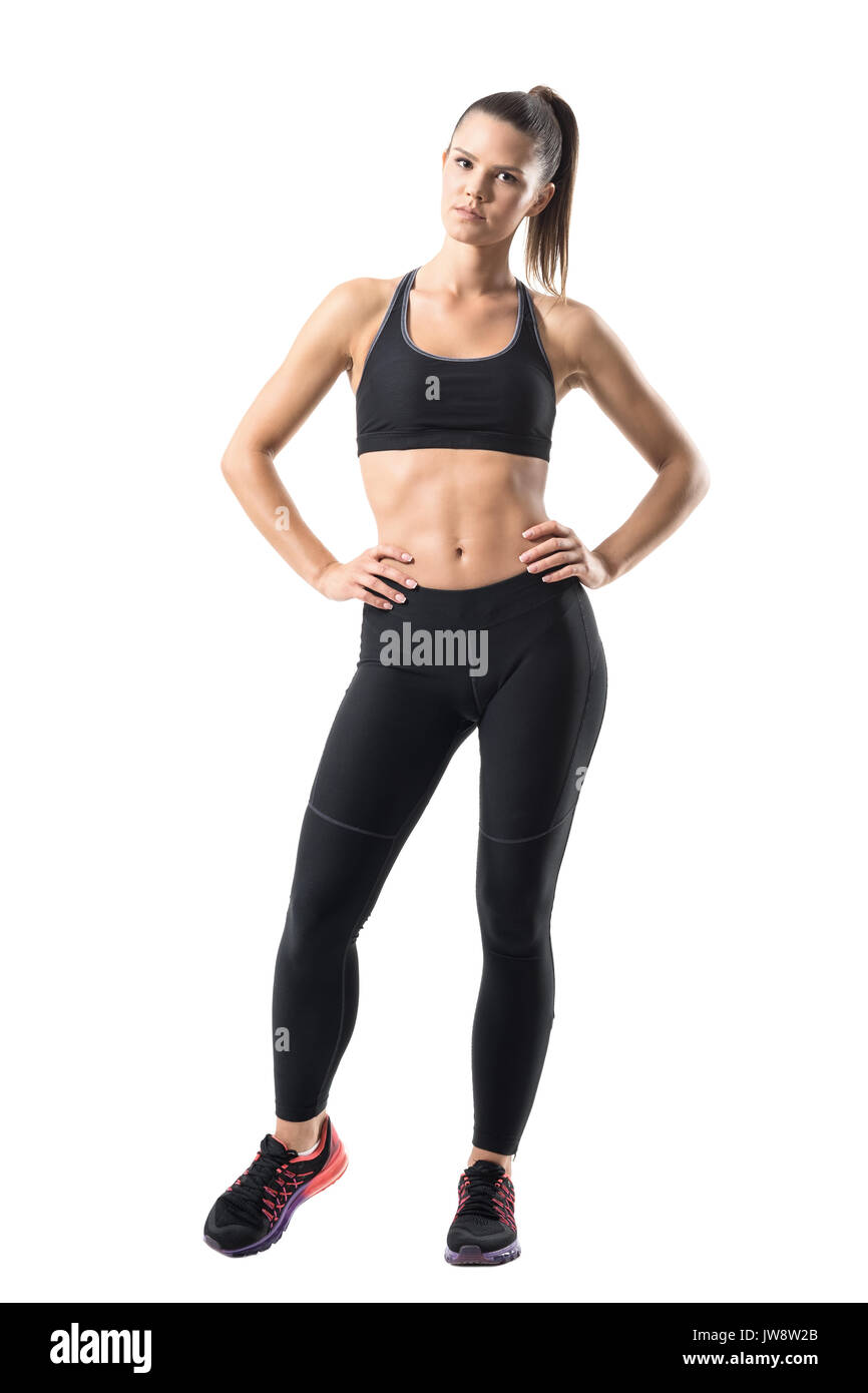 a61e7ebbcd Fitness young pretty woman in black leggings and tank top posing with hands  on hips. Full body length portrait isolated on white studio background