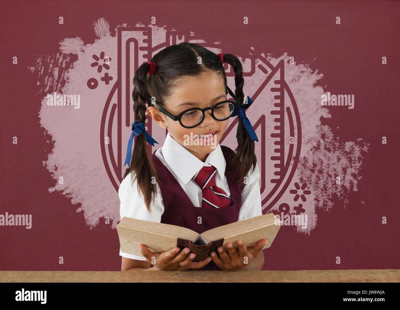 Digital composite of Student girl at table reading against red blackboard with education and school graphic Stock Photo