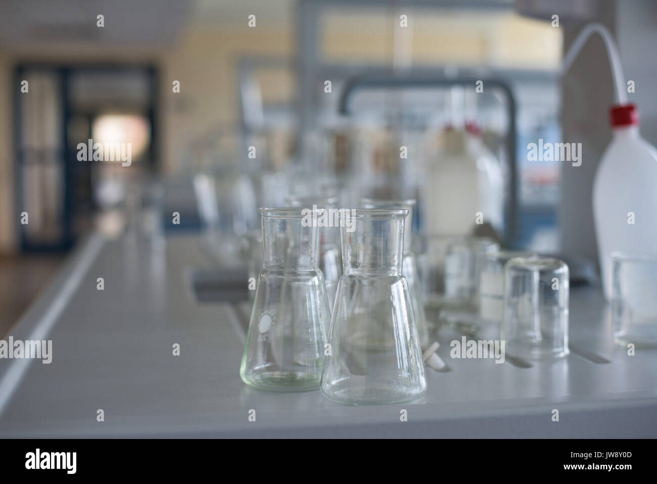 Close up of beakers on desk in lab - Stock Image