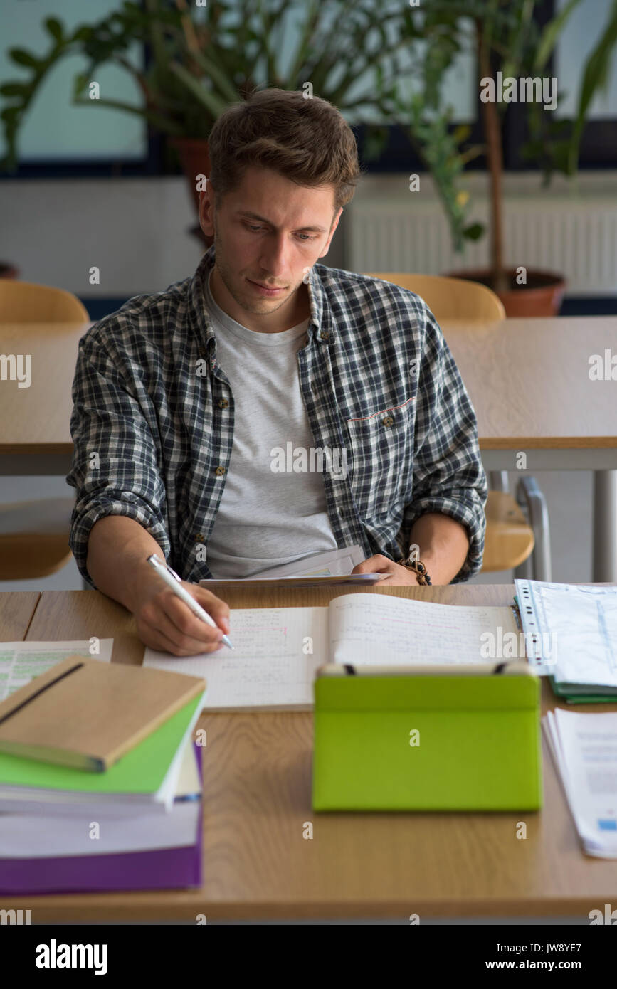 High angel view of young man using digital tablet while sitting at desk in classroom - Stock Image
