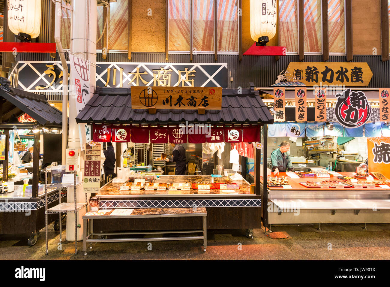 Two take-away seafood shops with open counters side by side in the indoor fresh food market, Omicho, at kanazawa, Japan. - Stock Image