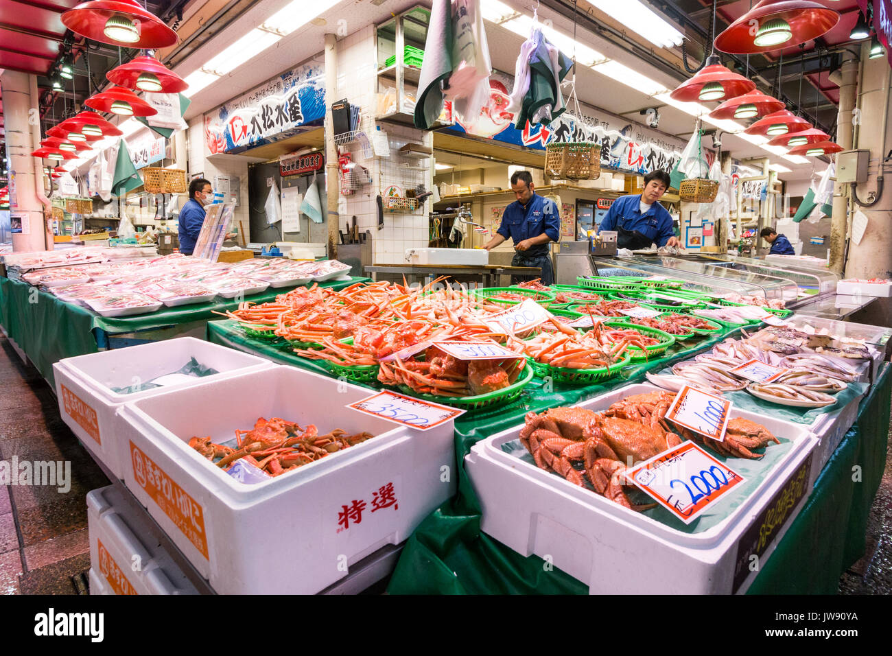 Containers filled with large orange crabs on sale on fish-mongers stall in the indoor fresh food market, Omicho, Kanazawa, Japan. - Stock Image