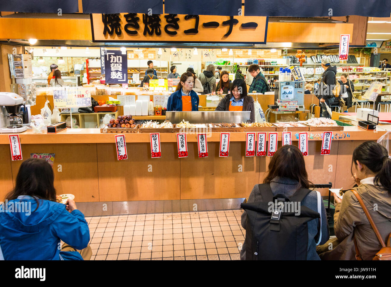 Fast food counter selling traditional Japanese snacks with menu tickets hanging from counter. Foreground, over the shoulder of customers eating. - Stock Image
