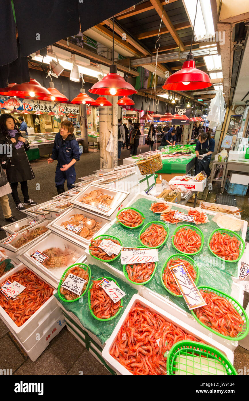 Prawns, in green plastic baskets, and crabs on sale on stall in the famous Omicho indoor fresh food market in Kanazawa, Japan. Some people. - Stock Image