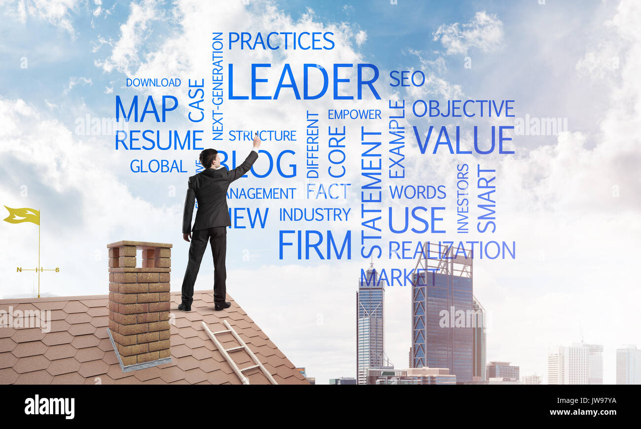 Young businessman standing on house roof and writing leadership skill concept. Mixed media - Stock Image
