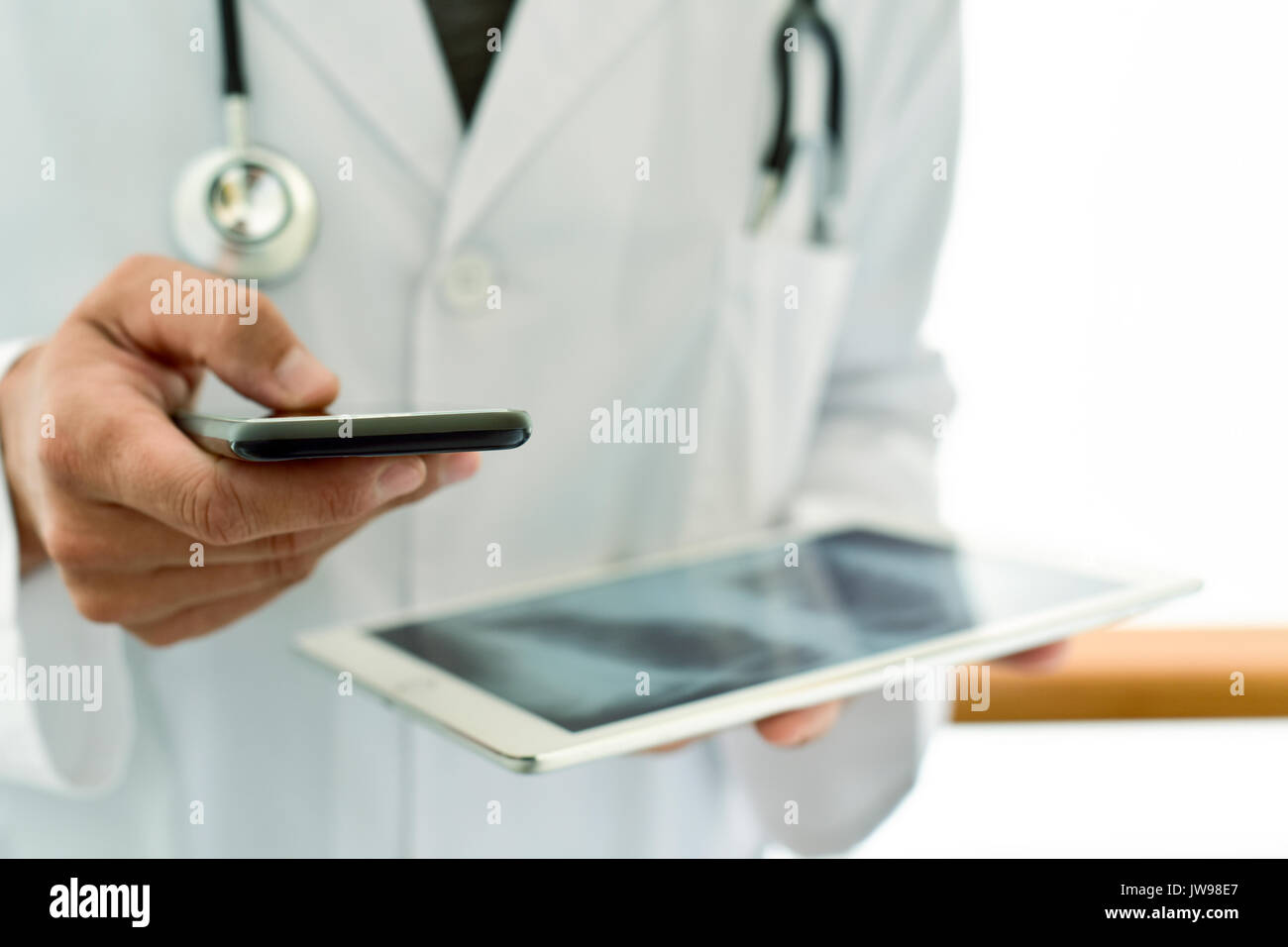 closeup of a young caucasian doctor man wearing a white coat using a smartphone while is checking a chest radiograph in a tablet computer - Stock Image