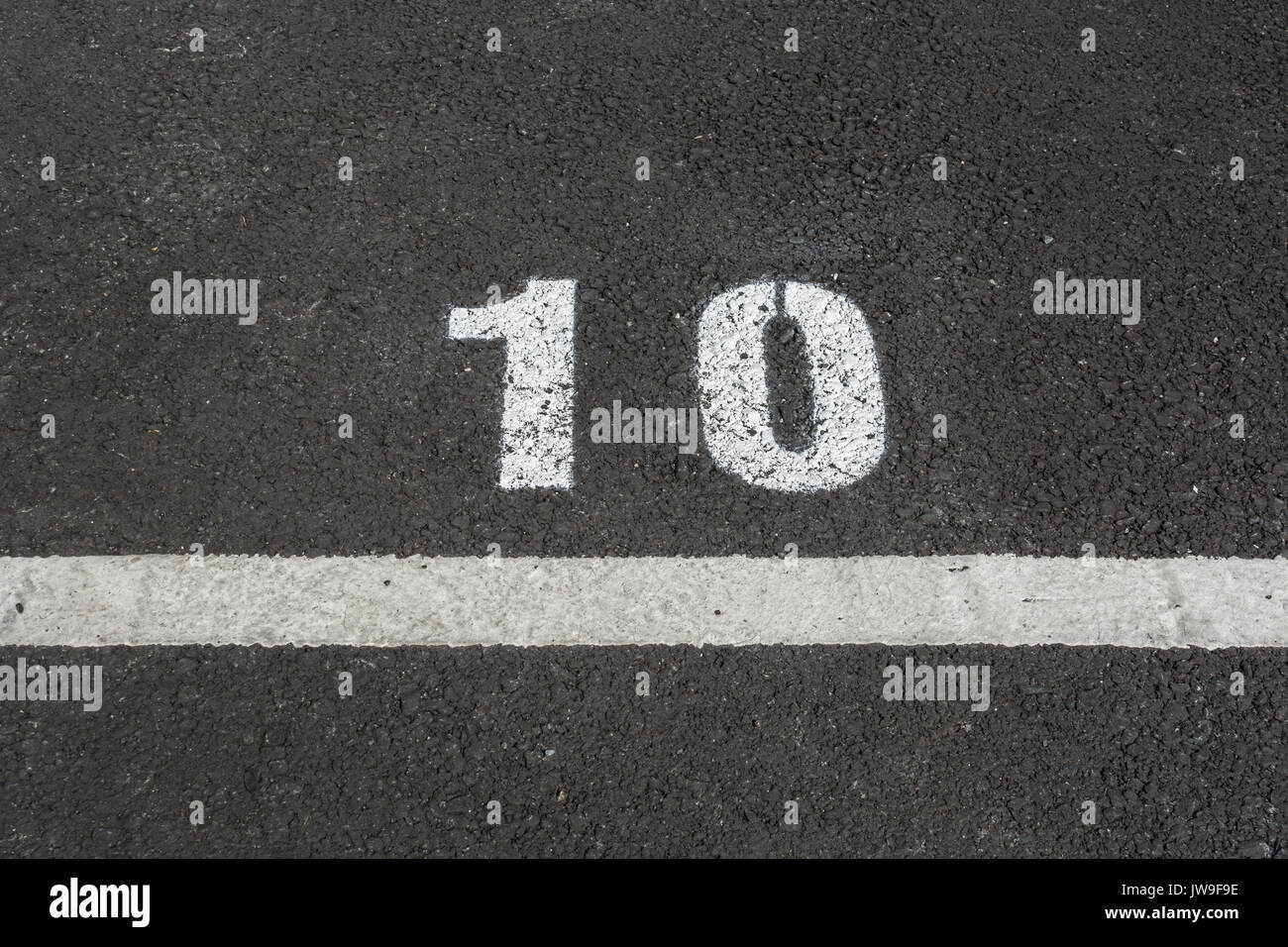 Painted number 10 on tarmac car park / parking lot space. Even number. - Stock Image