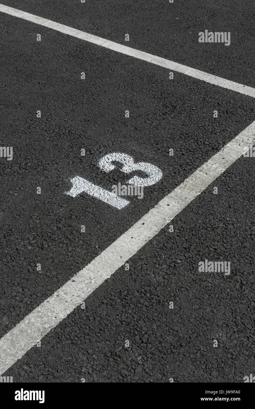Painted number 13 on tarmac car park / parking lot space. Bad luck and 13 are well-known connection. Odd number. - Stock Image