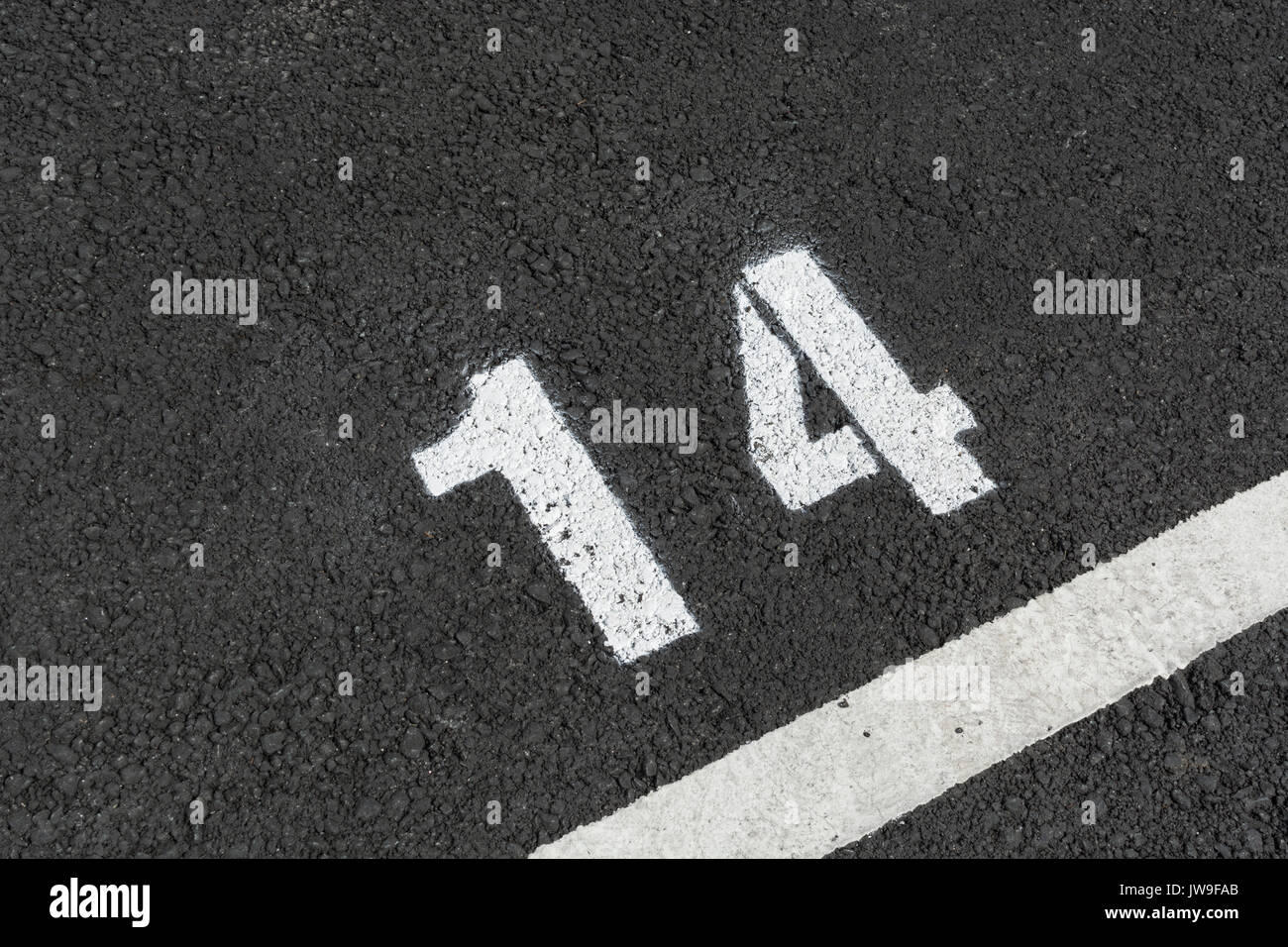 Painted number 14 on tarmac car park / parking lot space. Even number. - Stock Image
