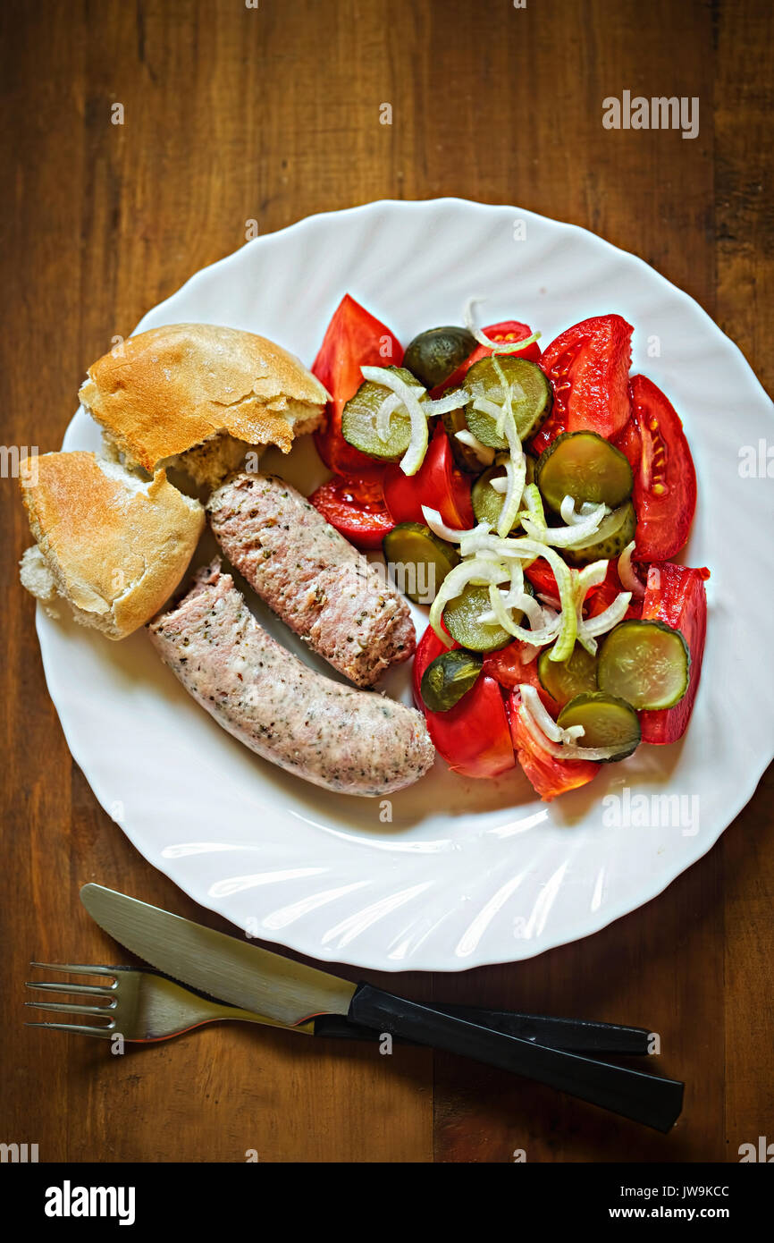 White sausage with gherkin, tomato, onion salad and fresh roll - Stock Image