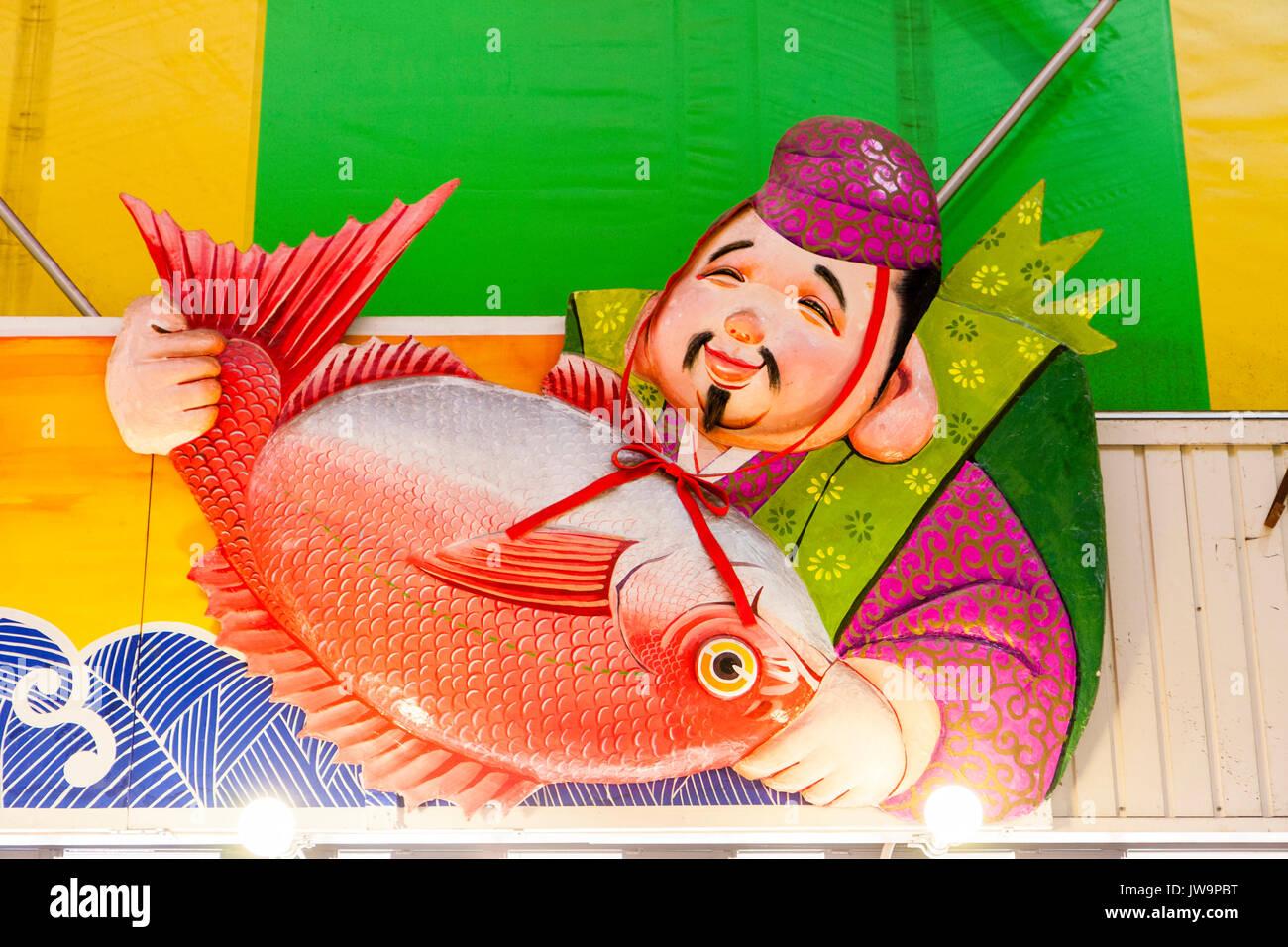 Japan, Kanazawa. Omi-cho fresh food indoor market. Fresh fish stall.Sign above store, Ebisu, Japanese God of Fishermen, holding large orange fish. - Stock Image