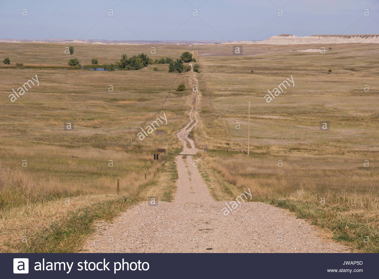 A primitive dirt road cuts far across the Badlands prairie. - Stock Image