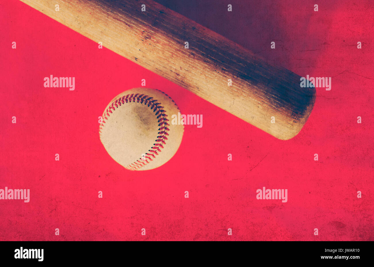 Wood baseball bat and game ball against red grunge background. - Stock Image