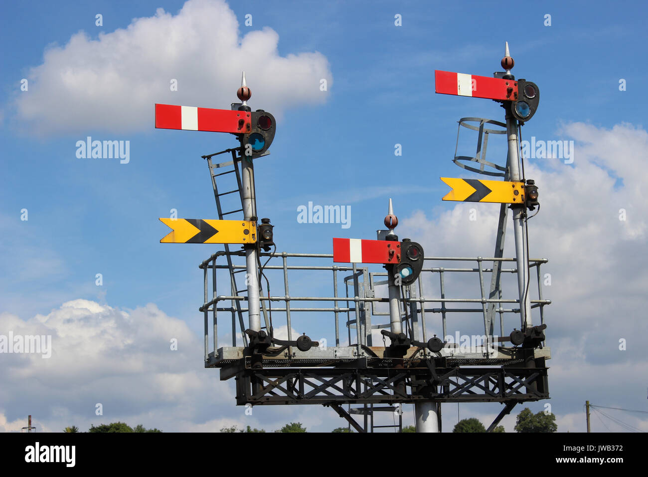Set of semaphore signals on a gantry at one end of Worcester Shrub Hill railway station seen against a mainly blue Stock Photo