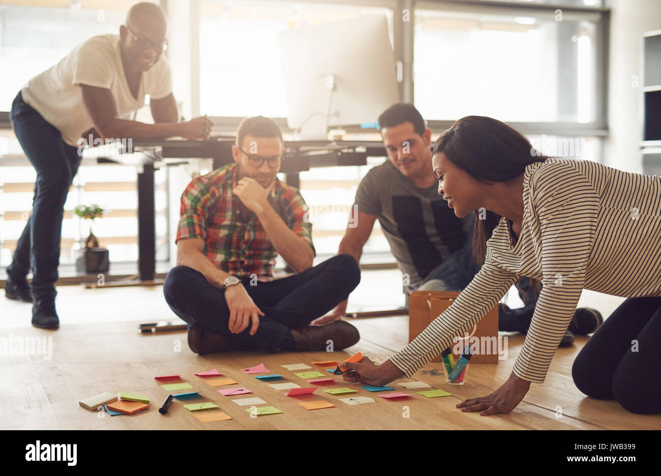 The modern cheerful group of office workers sitting and planning while the meeting. - Stock Image