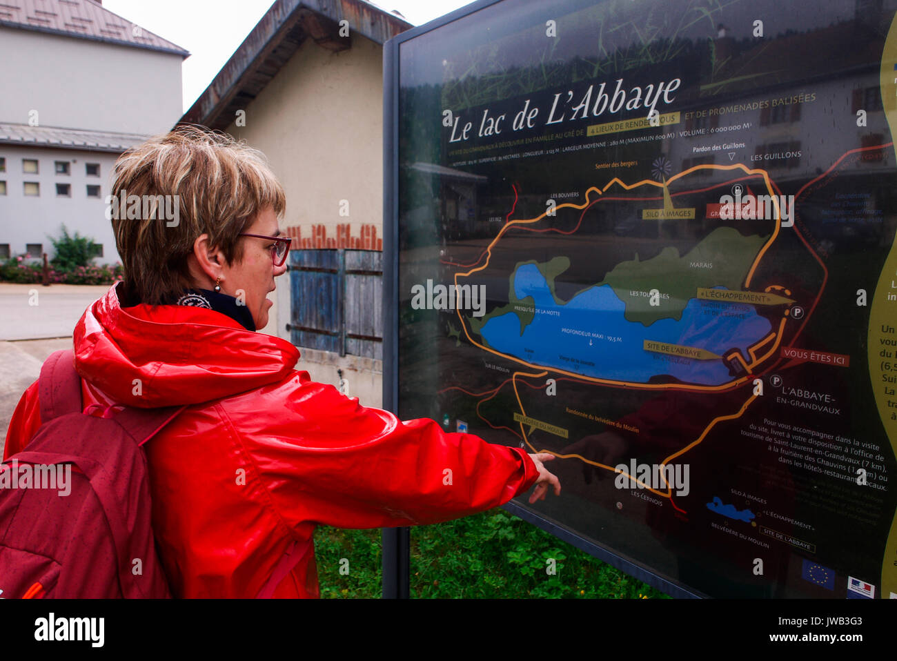 A woman looks to a touristic map of Granvaux Lake, Franche-Comté,  (France) Stock Photo