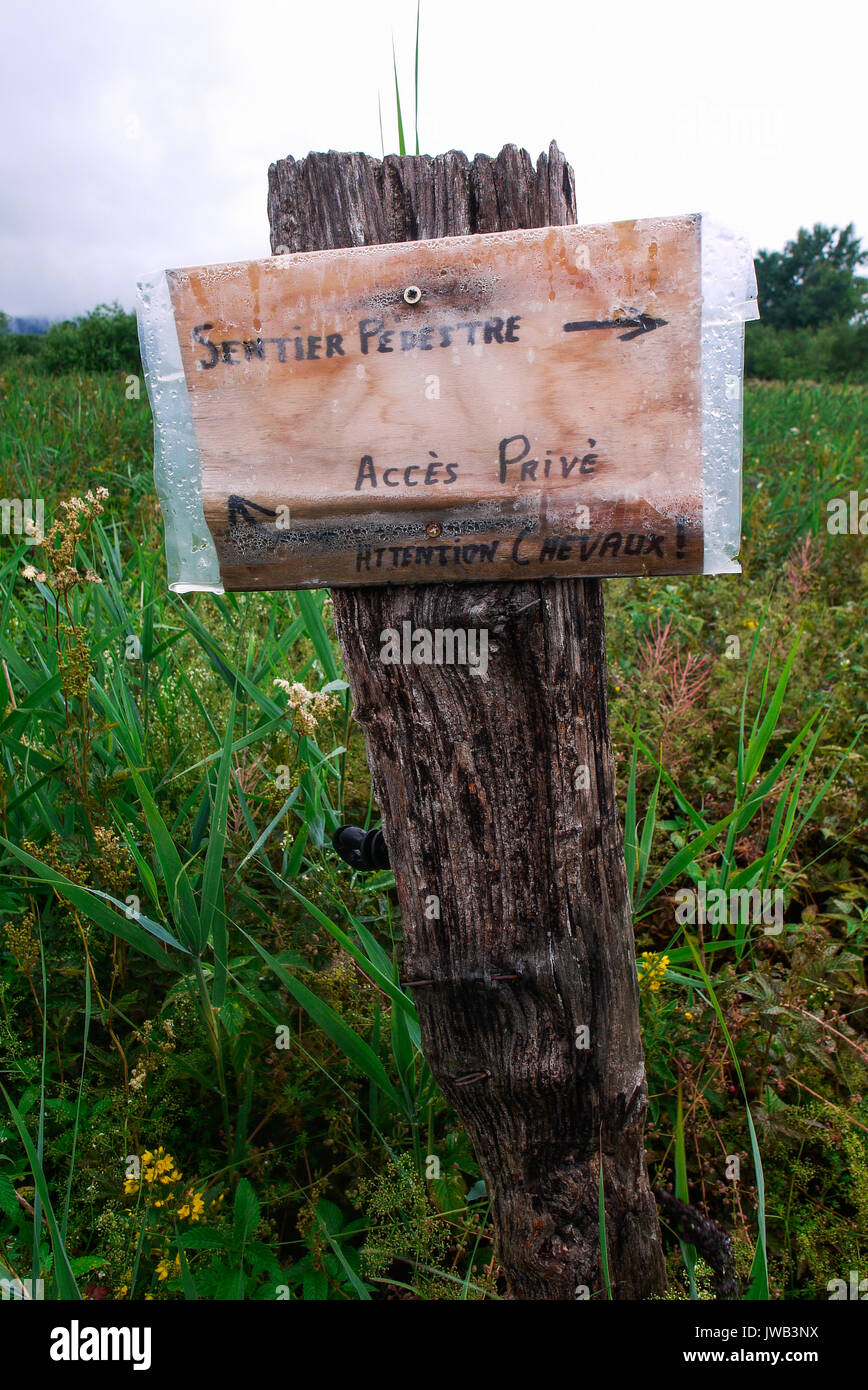 A sign guides tourists on a footpath at Grandvaux Lake, Franche-Comté,  Jura (France) - Stock Image
