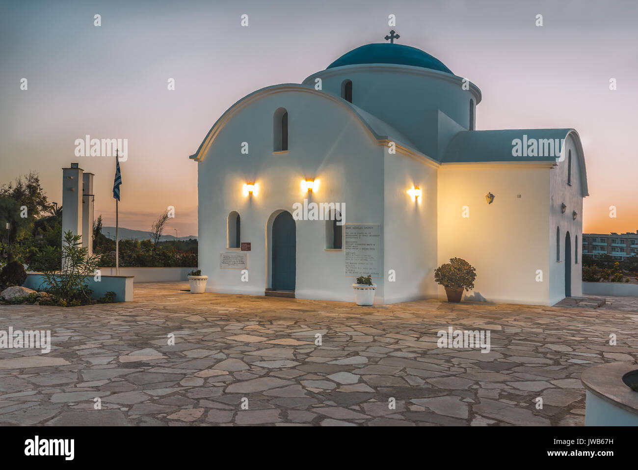 A small white church on the beach in Paphos, Cyprus during the dawn. The sun rises above the horizon and illuminates the church. - Stock Image