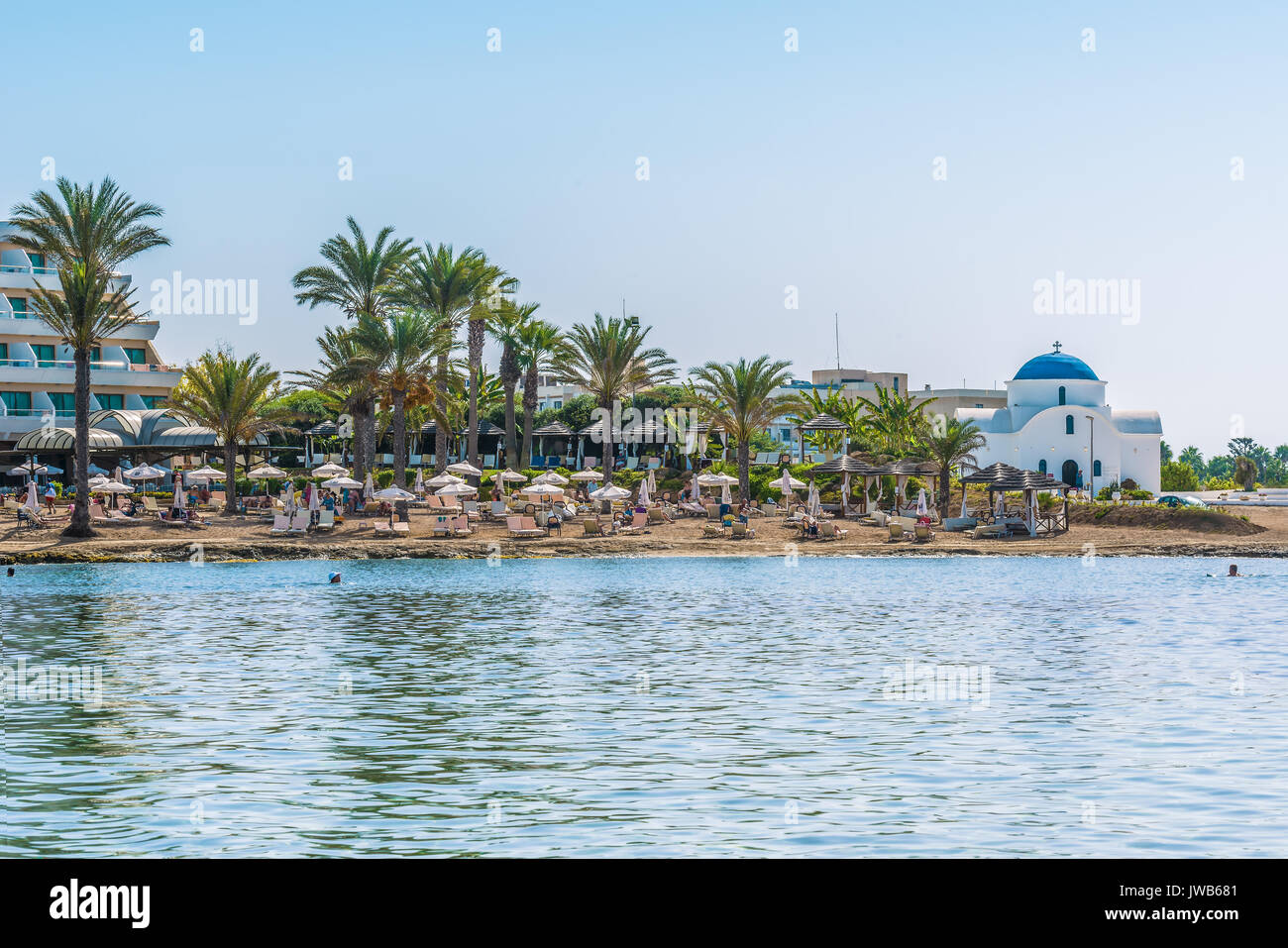 Paphos, Cyprus - September 20, 2016: View of the beautiful beach in Paphos, Cyprus. A fragment of the Mediterranean Sea and a small white Orthodox chu - Stock Image