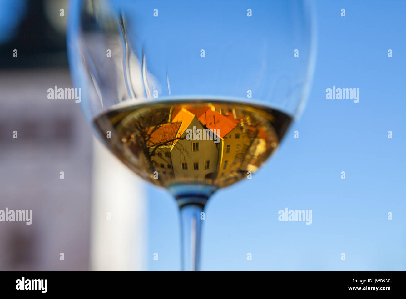 Glasse of white wine with old Tallinn view in reflection - Stock Image