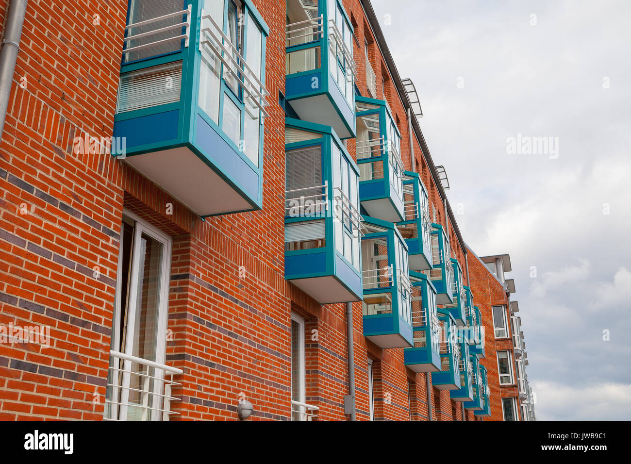 Fragment of new brick building wall with windows and blue balconies. Modern apartment house. - Stock Image