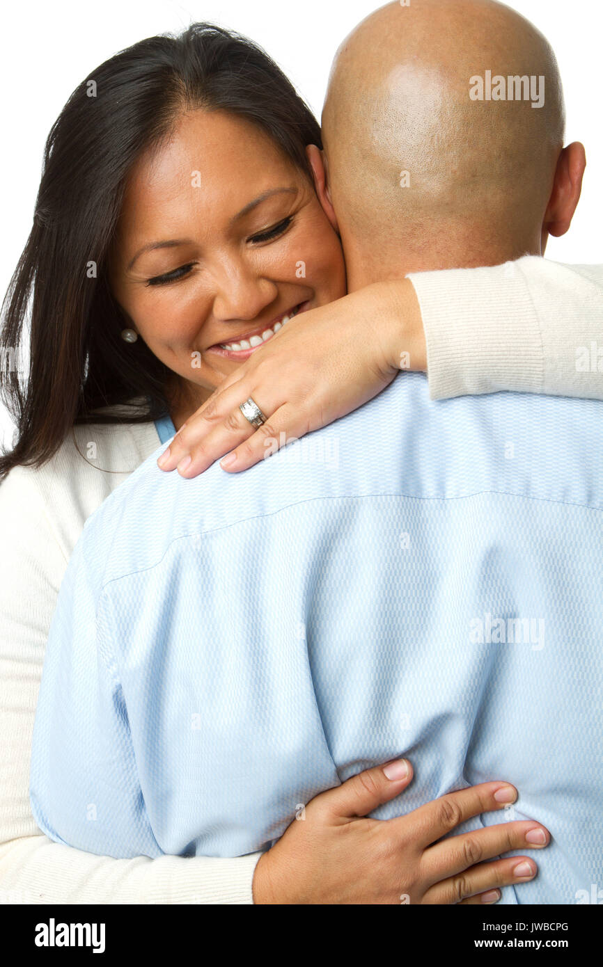 Rear view of a woman hugging her husband isolated on white. - Stock Image