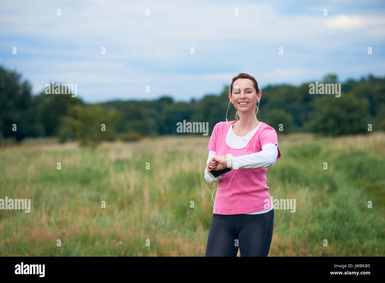 A healthy, smiling woman in fit wear with smart phone, watch and earphones, exercising outdoors in nature. Stock Photo