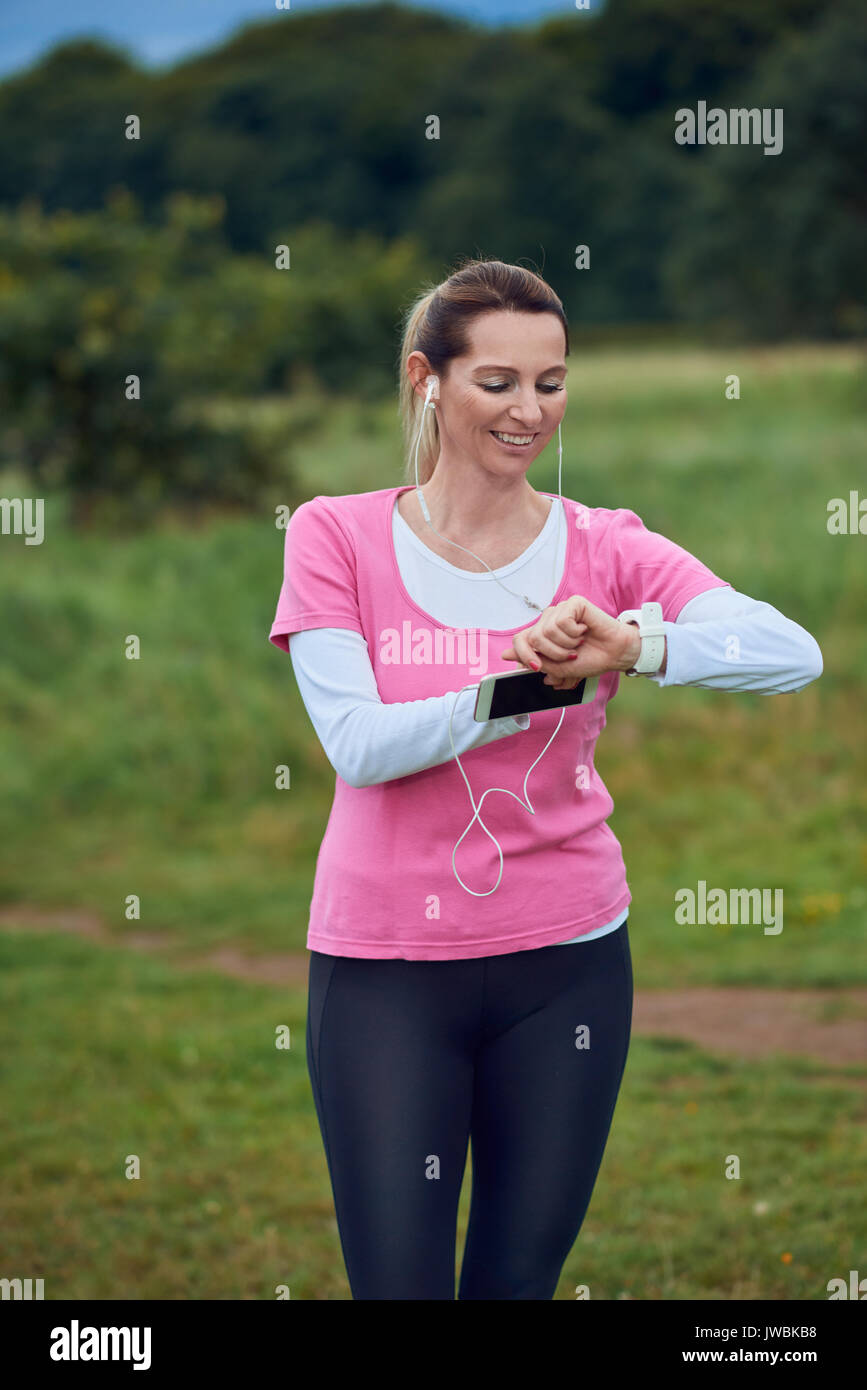 Middle-aged woman checking her sport or health watch while out jogging in the countryside listening to music on her mobile phone in a healthy lifestyl - Stock Image