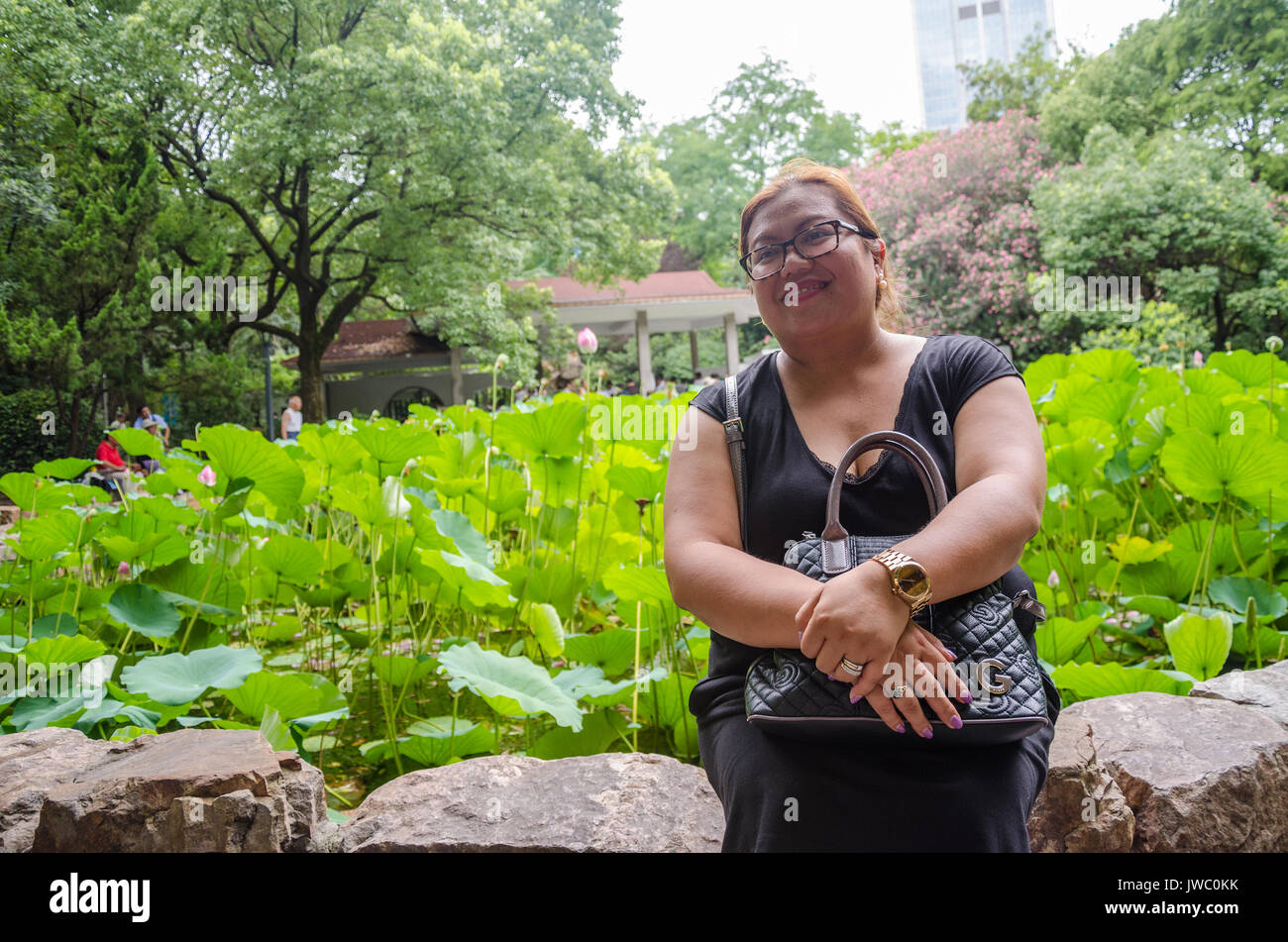 A lady sits and poses for a portrait in front of a pool of lotus flowers in People's Park in Shanghai, China. - Stock Image