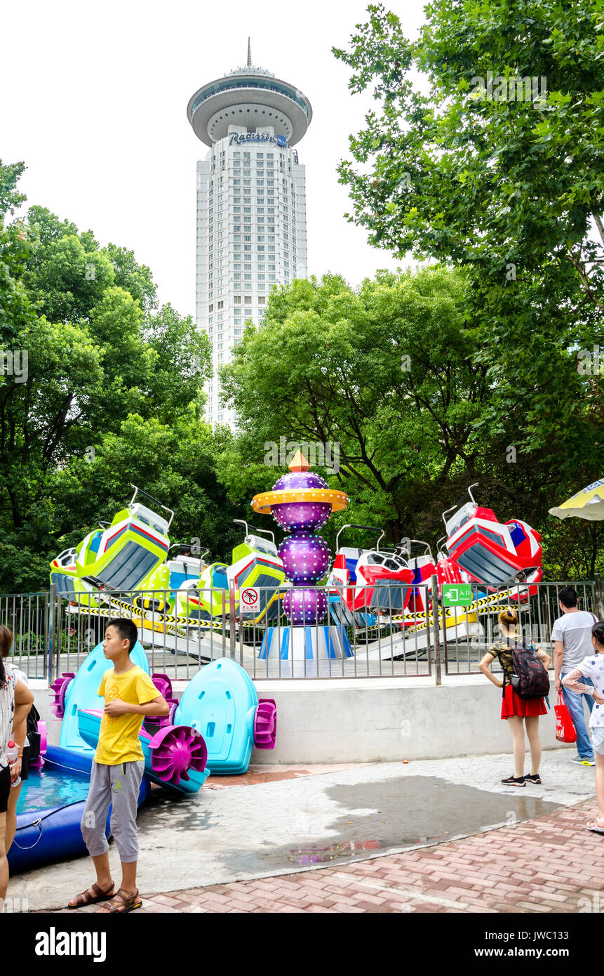 The Radisson Blu looms tall in the background behind children's rides in The People's Park in Shanghai, China. - Stock Image