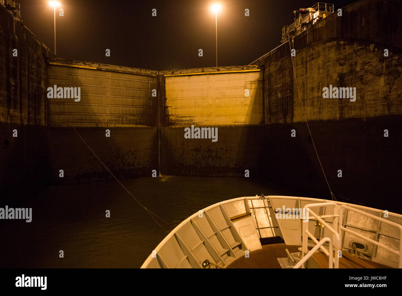 A cruise boat is tied to guiding train engines as the vessel enters Gatun Locks from the Atlantic entrance of the Panama Canal. - Stock Image