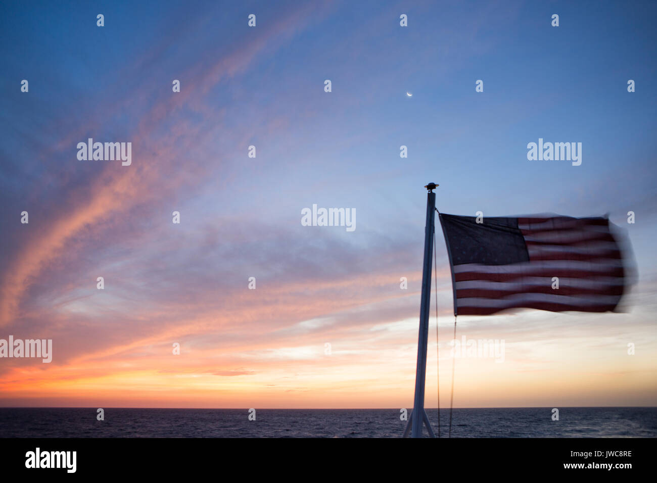 Over the waters near Isla Coiba National Park,a sliver of moon is visible as the sunrise illuminates the sky,clouds and an American Flag that flies from the National Geographic Sea Lion. - Stock Image