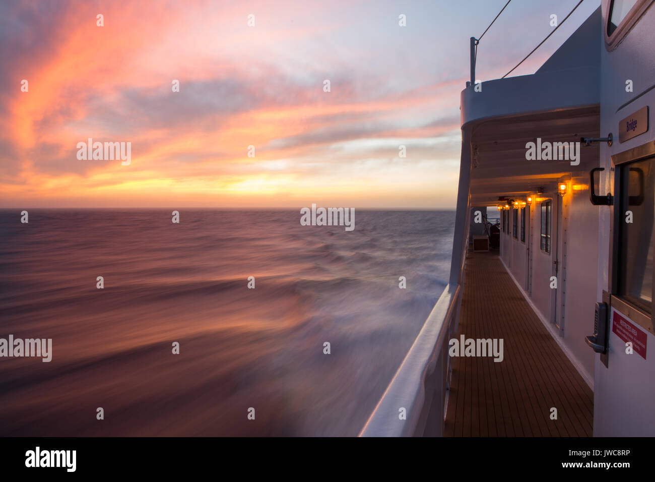 The rising sun illuminates clouds above the waters near Isla Coiba National Park as an expedition cruise ship,the National Geographic Sea Lion,speeds through the water. - Stock Image