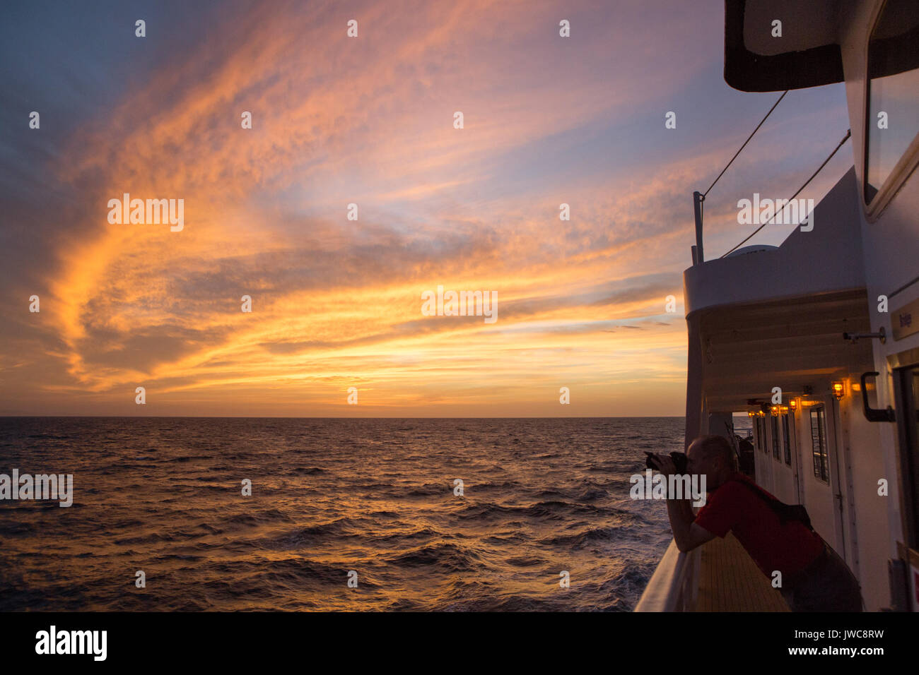 The rising sun illuminates clouds above the waters near Isla Coiba National Park as a passenger aboard the National Geographic Sea Lion photographs the surrounding landscape. - Stock Image