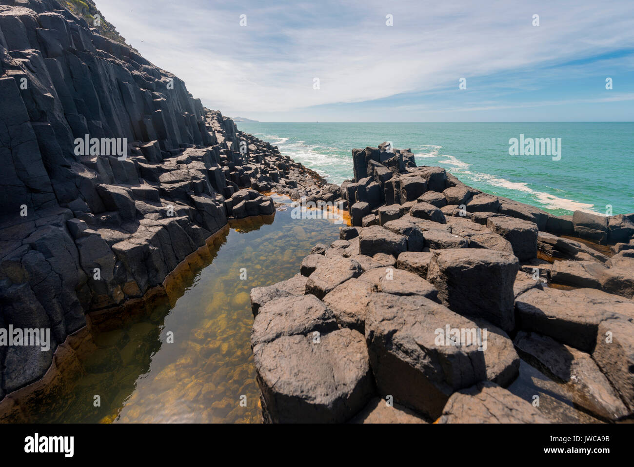 Water gathering between rocks, Roman Bath, Hexagonal basalt column by the Sea, Blackhead, Dunedin, Otago, South Island - Stock Image
