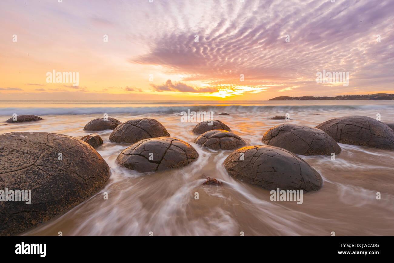 Moeraki boulders, at sunrise, geological formation, Koekohe Beach, Moeraki, East Coast, Otago, South Island, New Zealand - Stock Image
