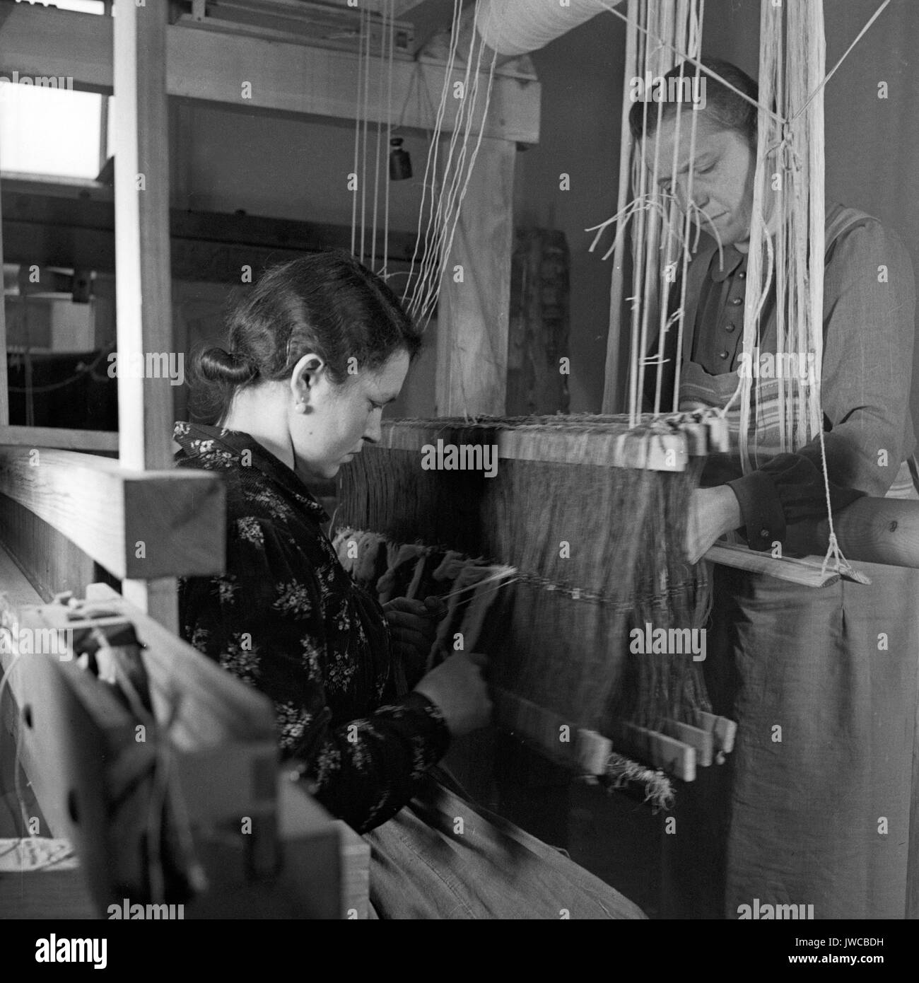 Two women working with weaving loom. - Stock Image
