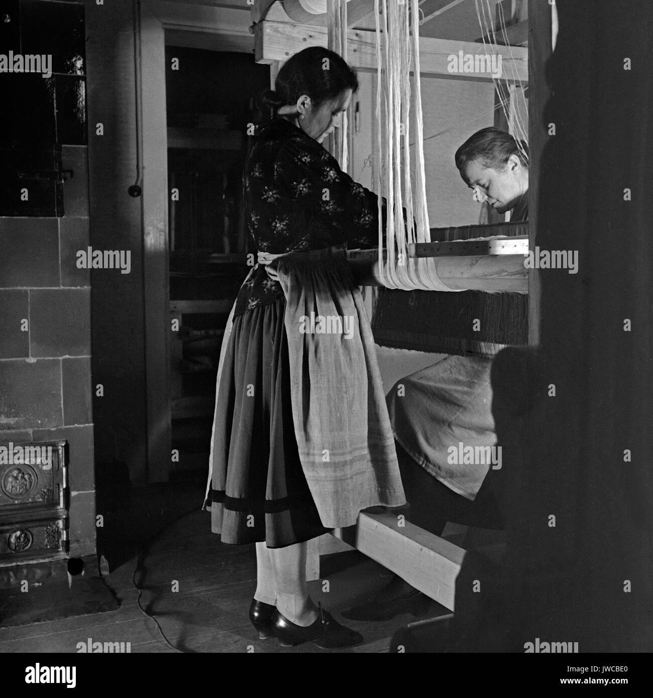 Two women weaving. - Stock Image