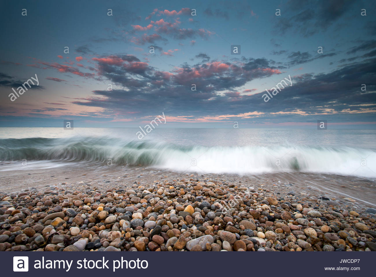 Waves wash ashore under a gentle sky. - Stock Image