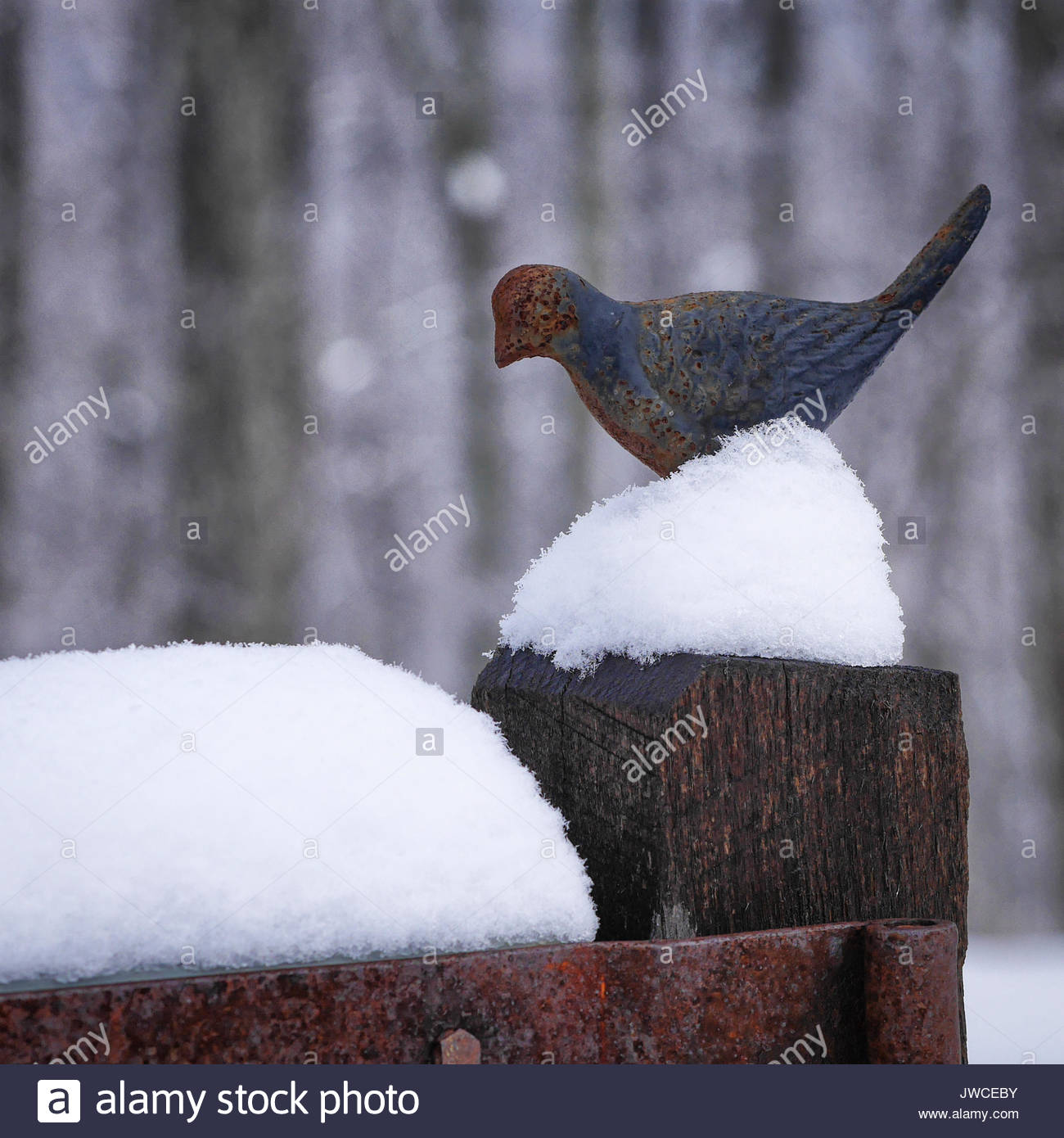 An iron bird ornament tops a fence post that is covered in snow. - Stock Image