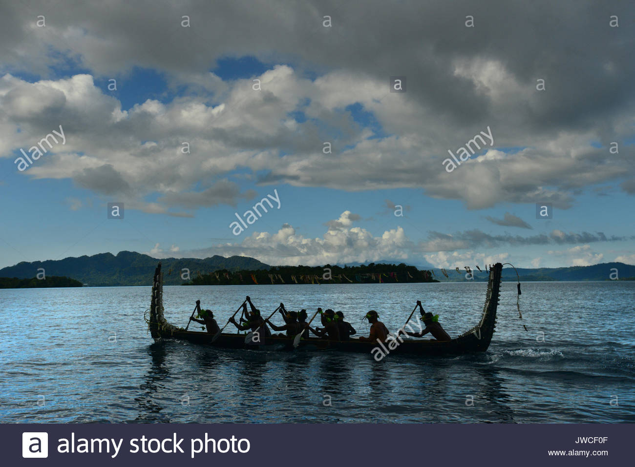 Men rowing in a traditional ceremonial canoe. - Stock Image