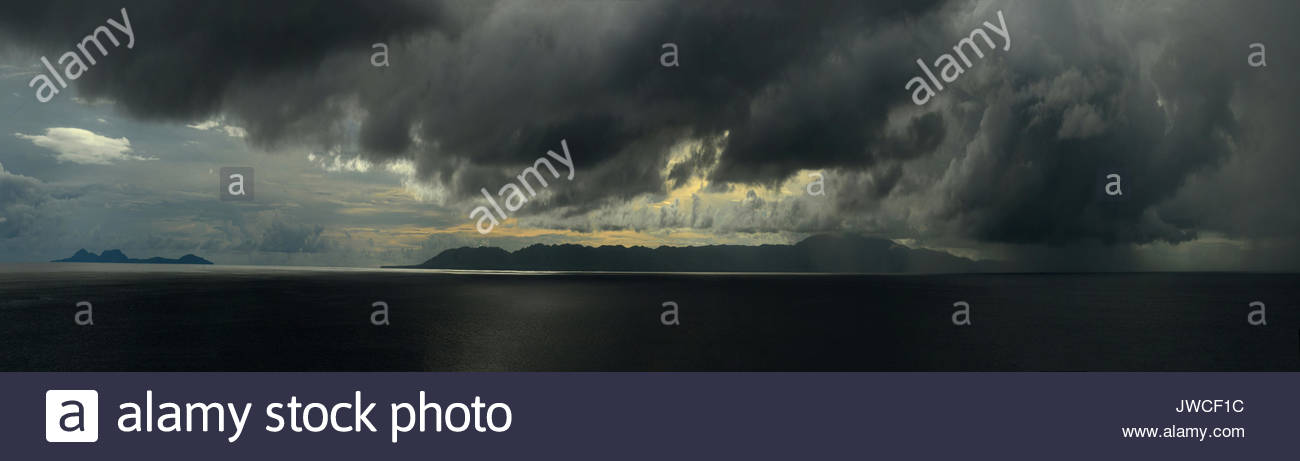 Squall at sunrise over the island of Gizo. - Stock Image
