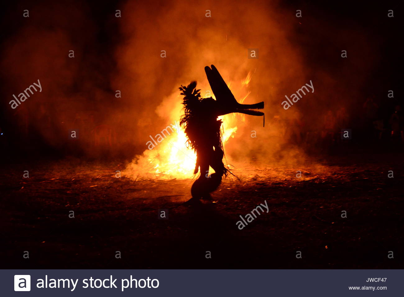 A costumed person in silhouette in front of a fire during a Baining fire dance. Stock Photo