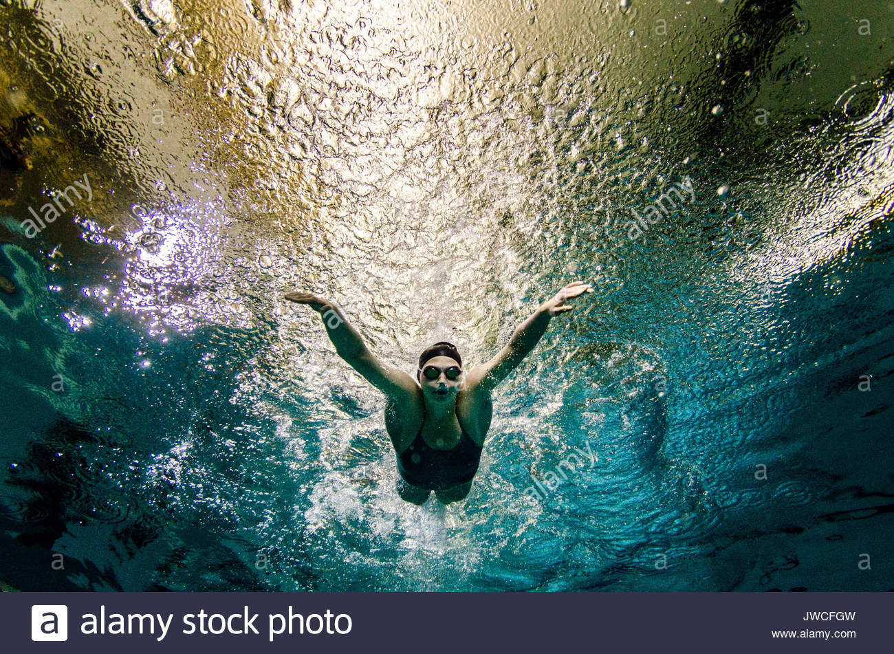 A young woman in a green bathing suit, black swim cap, and goggles, swims the butterfly stroke. - Stock Image