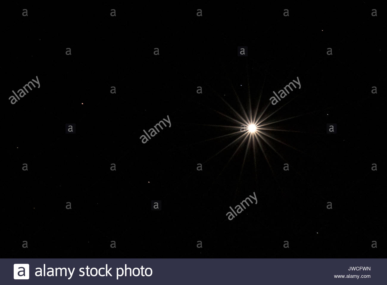 Venus in the night sky with diffraction spikes formed by the lens aperture diaphragm. - Stock Image