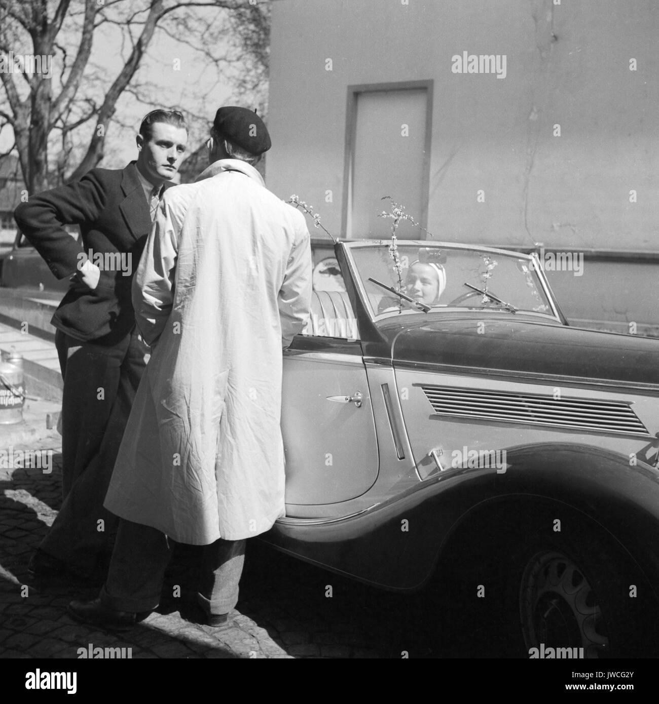 Two men talking beside parked car. - Stock Image