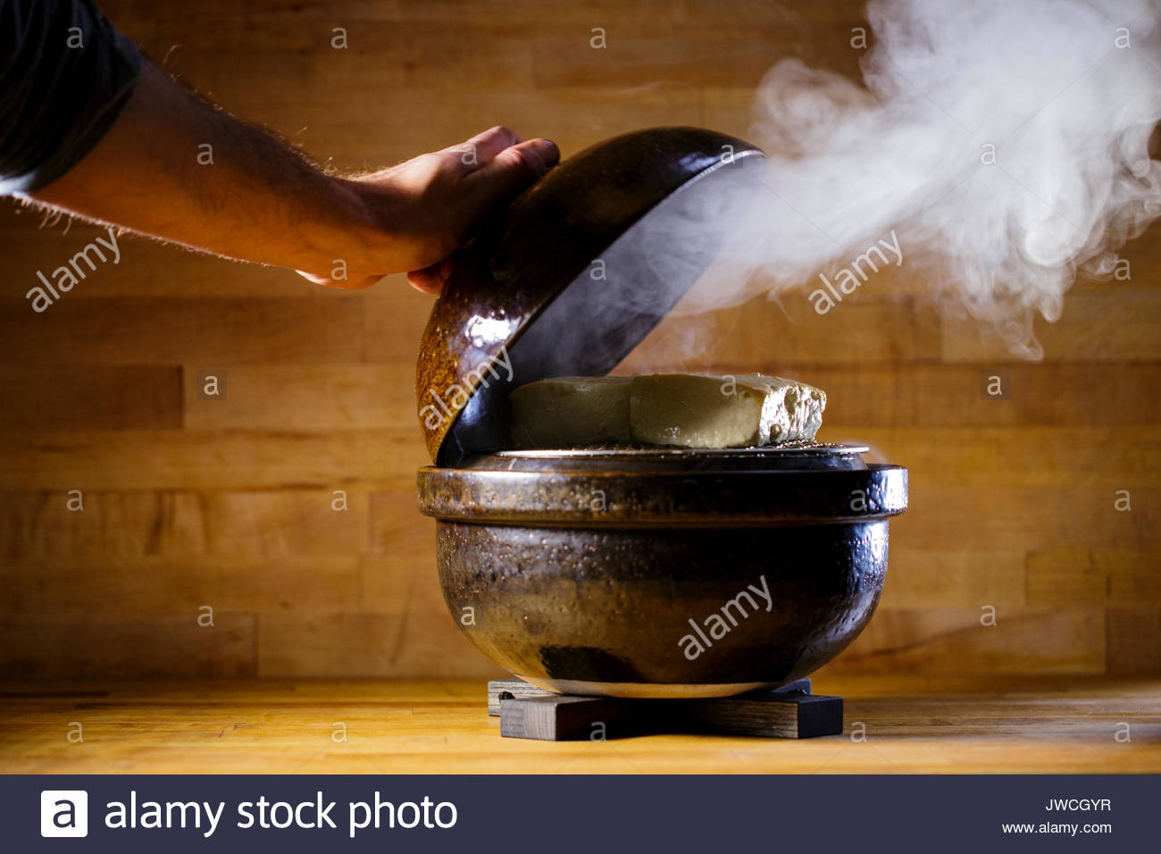 A chef reveals smoked tofu in a donabe, a traditional form of Japanese cookware. - Stock Image