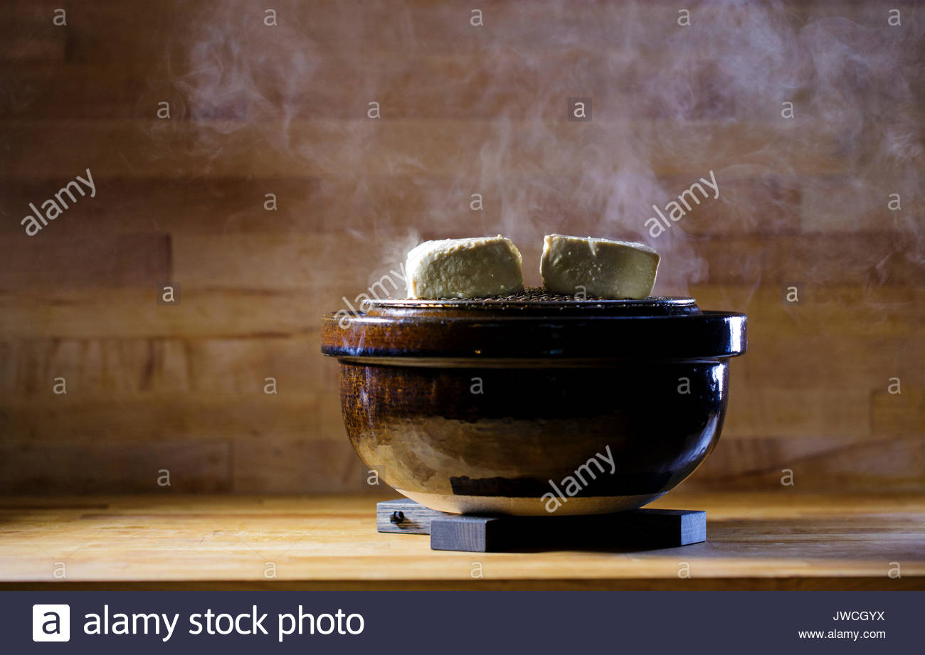 Smoked tofu rests on top of a donabe grill, a specialized form of Japanese cookware. - Stock Image