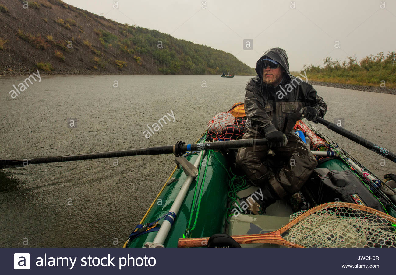 Alaska fishing guide rows a raft during an autumn squall in far west Alaska. - Stock Image