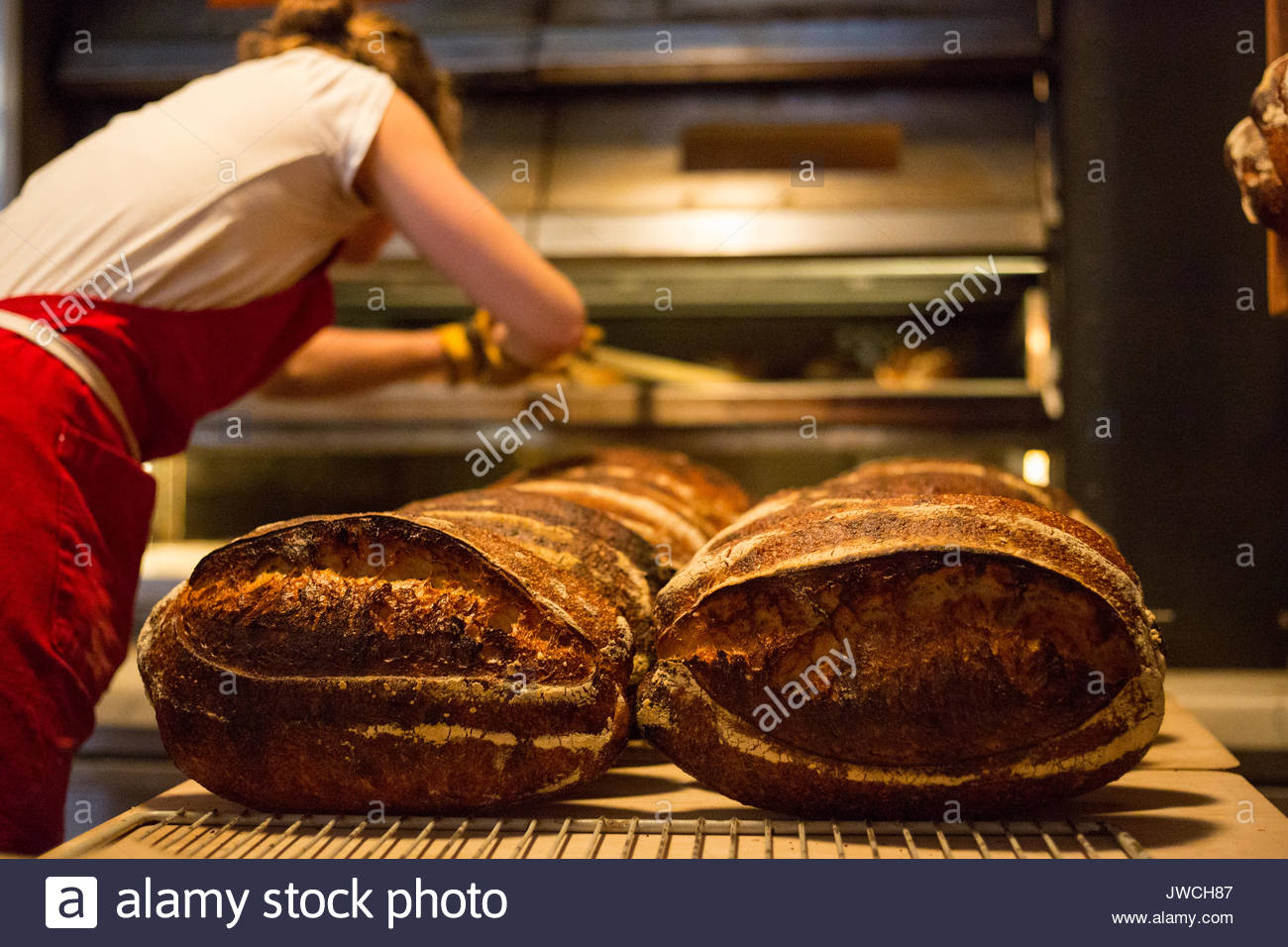 An artisan baker removes fresh loaves of bread from an industrial oven. - Stock Image